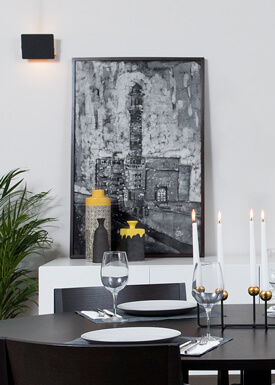 The interior styling of a modern meets classic apartment in a black-white-grey theme with accents of gold and yellow.