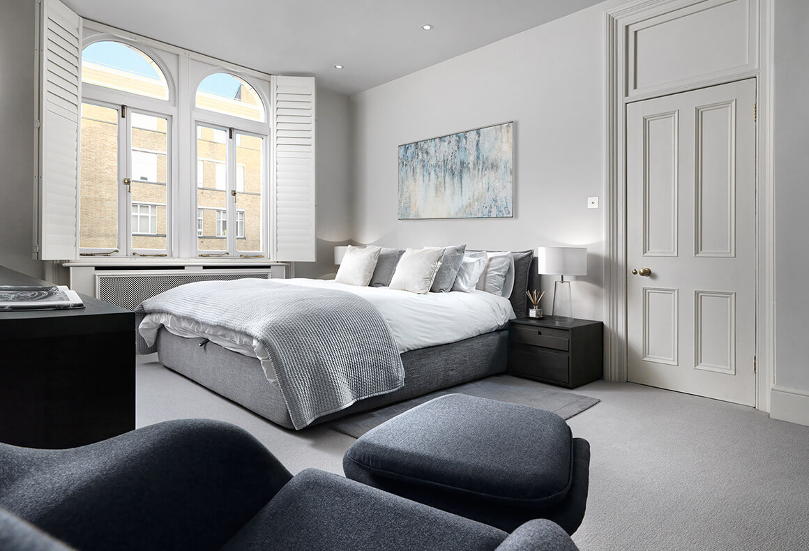 A peaceful minimalist monochrome grey bedroom with subtle classic touches.