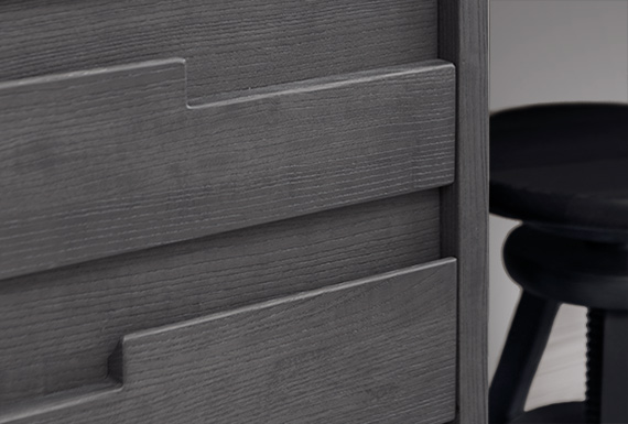 A closeup view of a bespoke grey bedside table showing the drawer handle detail.