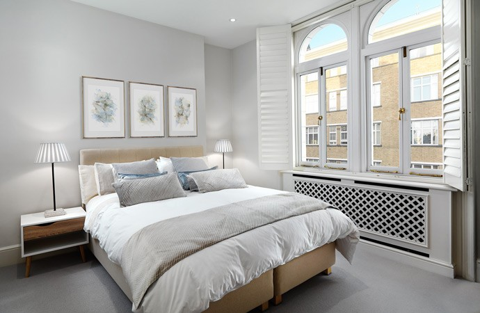 A soothing bedroom interior in light grey and sand tones.