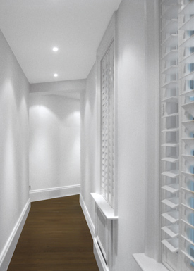 A renovated apartment corridor with repaired walls, a new false ceiling with spotlights, and wooden floors.