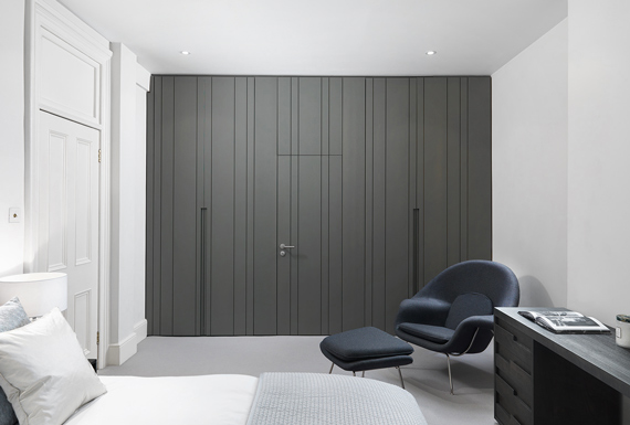 A floor-to-ceiling built-in wardrobe designed with vertical matte grey lacquered panels which create a feature wall.