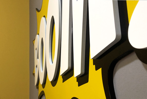 A closeup view of a multi-tiered 3D acrylic sign that says boom in black, white and yellow.
