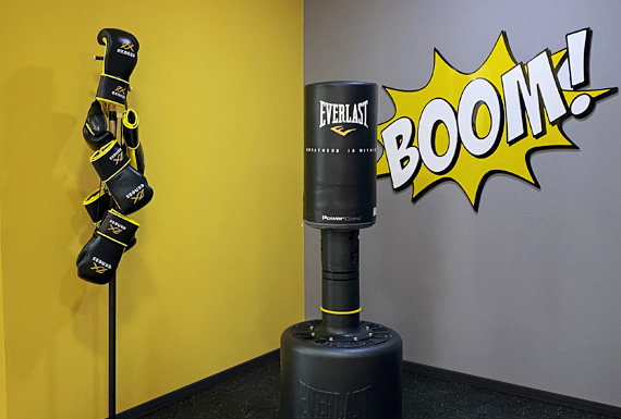 A yellow and grey boxing corner with a floor-standing punching bag, branded boxing gloves and an acrylic sign that says boom.