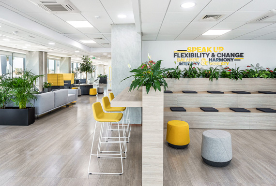 A branded office design for Exness forex offices with a yellow theme, diverse work areas and wall graphics.