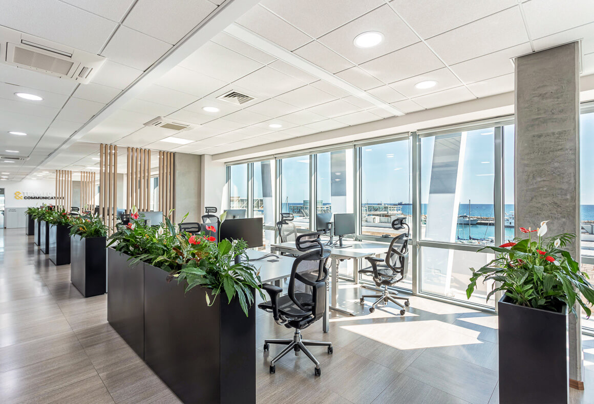 A modern and airy office design for Exness, with open plan workstations in front of floor-to-ceiling windows with a sea view.