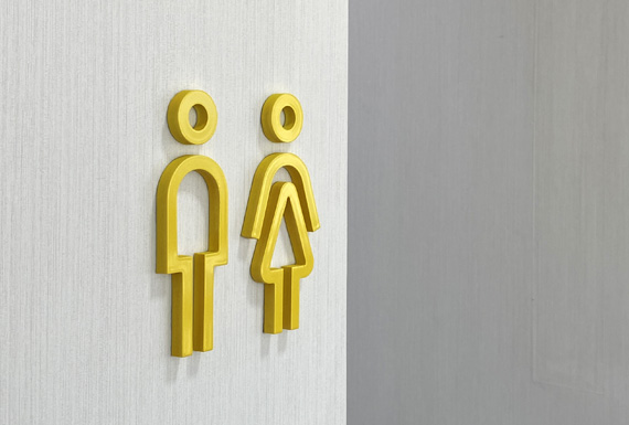 A custom yellow 3D WC sign which is part of a branded corporate wayfinding design.