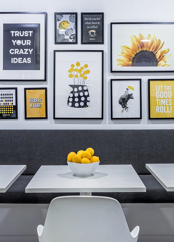 A gallery wall with black picture frames and prints with yellow accents above a casual eating area.