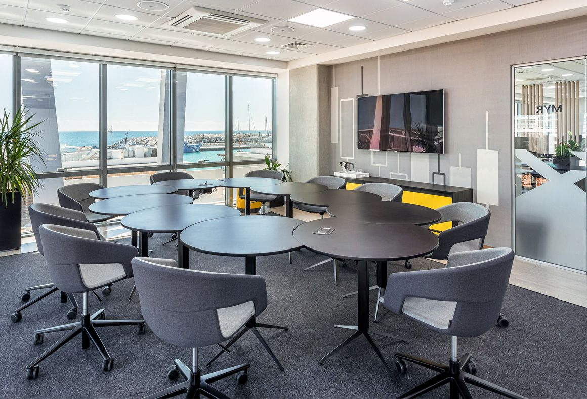 A black and grey conference room design for Exness offices with modular round tables, custom wallpaper and yellow accents.