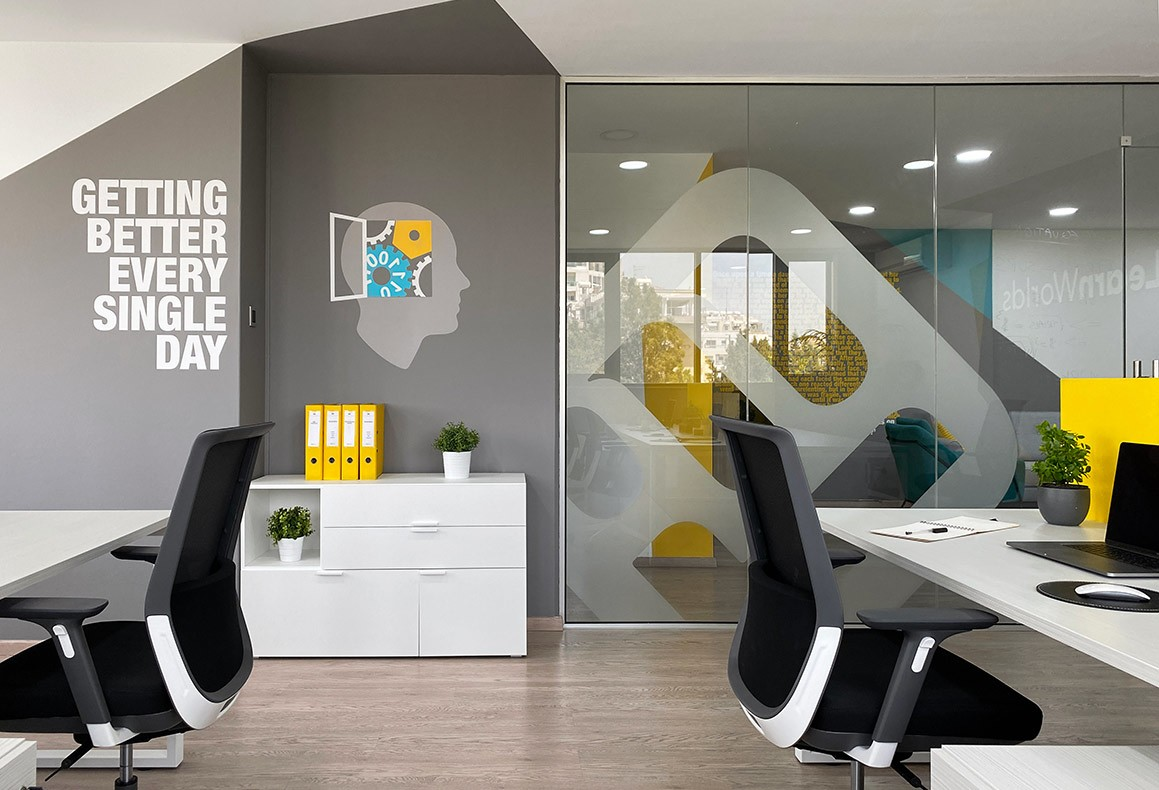 LearnWorlds' modern office interior in a yellow-teal-grey theme with white furniture and wall graphics.