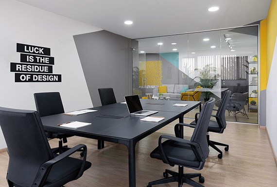 A modern office meeting room design for LearnWorlds, with glass partitions, geometric wall paint and black furniture.