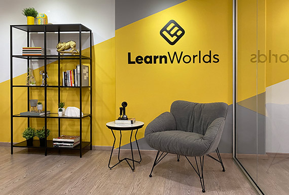 An office reading corner with a bookshelf and armchair in front of a diagonal yellow painted wall with the LearnWorlds logo.