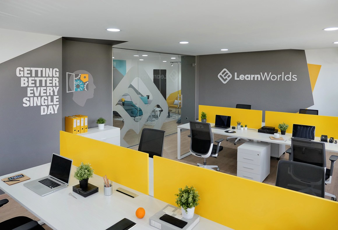 A yellow and grey themed open plan workspace for LearnWorlds offices.