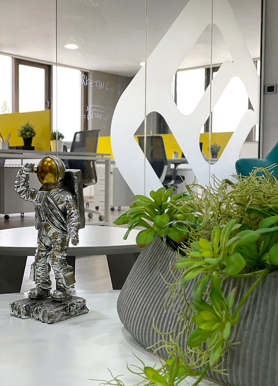 A closeup view of an astronaut decoration and planter in a modern office.