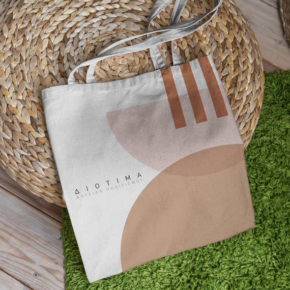 A branded tote bag for Diotima Cultural Institution with a geometric pattern in terracotta, peach and blush pink hues.