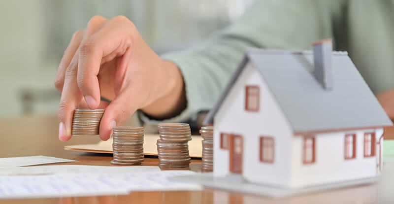 Eine Person stapelt Münzen neben einer Hausminiatur auf einem Tisch.