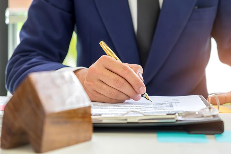 Eine Mann unterzeichnet Dokumente für den Hausverkauf. Symbolisch steht ein Holzhaus vor ihm auf dem Tisch.