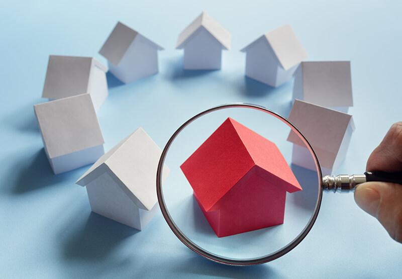 Mehrere weiße Hausmodelle sind kreisförmig aufgestellt. Das einzige rote Haus unter ihnen wird mit einer Lupe vergrößert betrachtet.