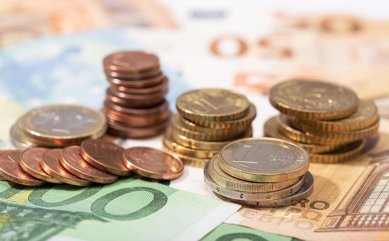 Nahaufnahme mehrerer Euro-Münzen auf verschiedenen Euro-Banknoten platziert.