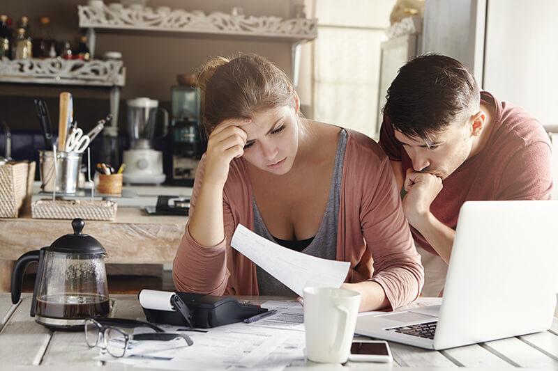 Junges Paar schaut sich verzweifelt rechtliche Dokumente an und scheint dabei Kosten zu kalkulieren.