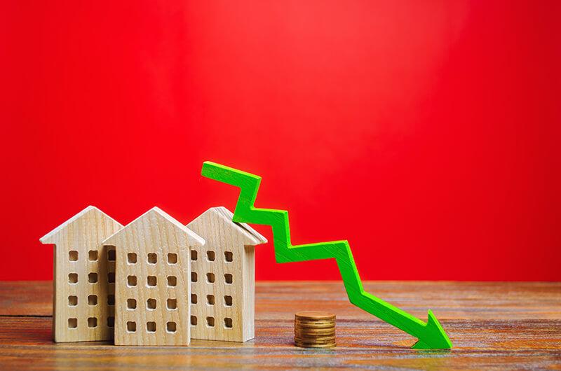 Holzhäuser stehen symbolisch auf einem Tisch. An ihnen liegt ein grüner Pfeil über einem Münzstapel, der fallende Zinsen verdeutlichen soll.