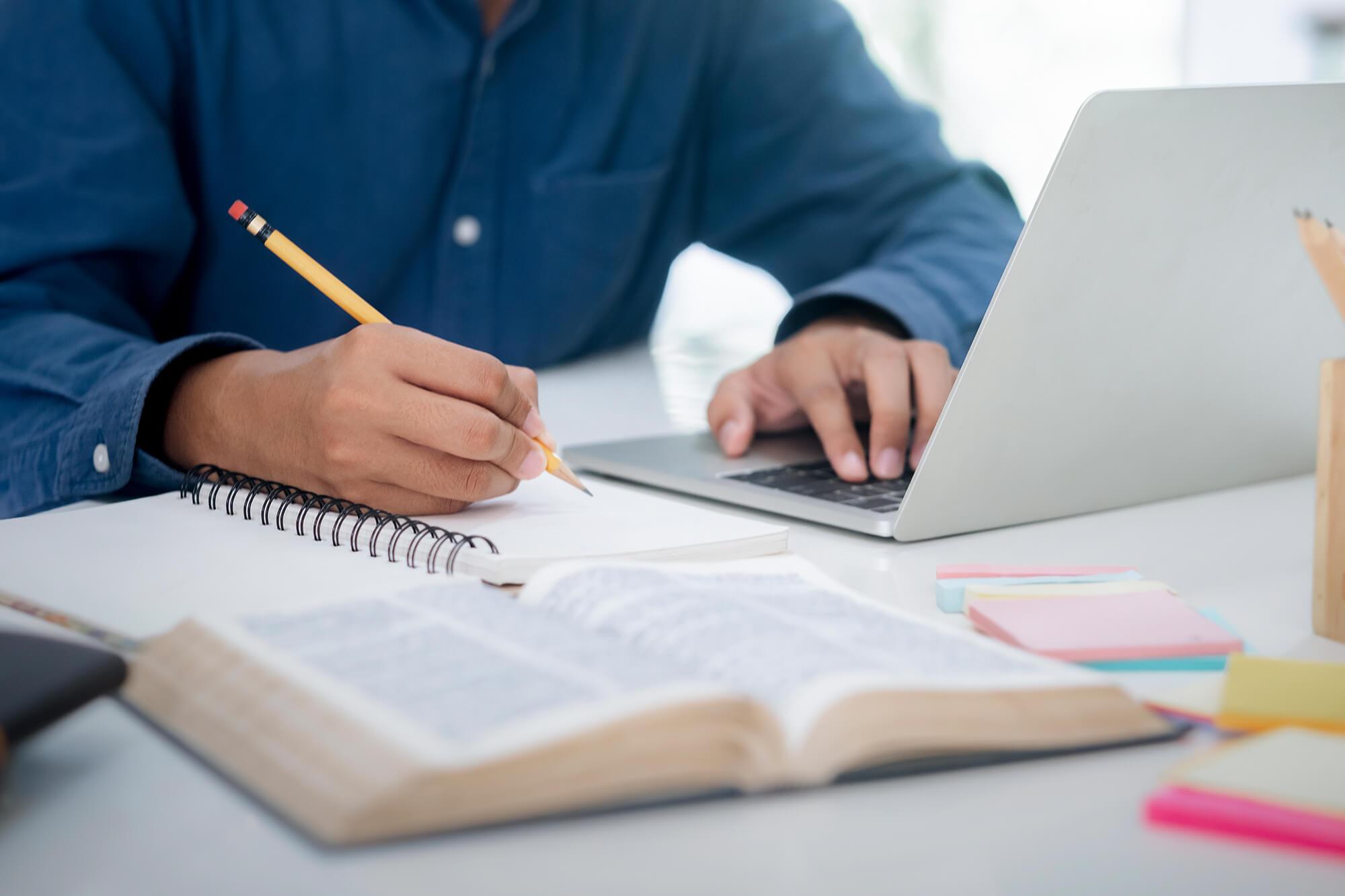 Person lernt mit einem Laptop, Büchern und einem Schreibblock