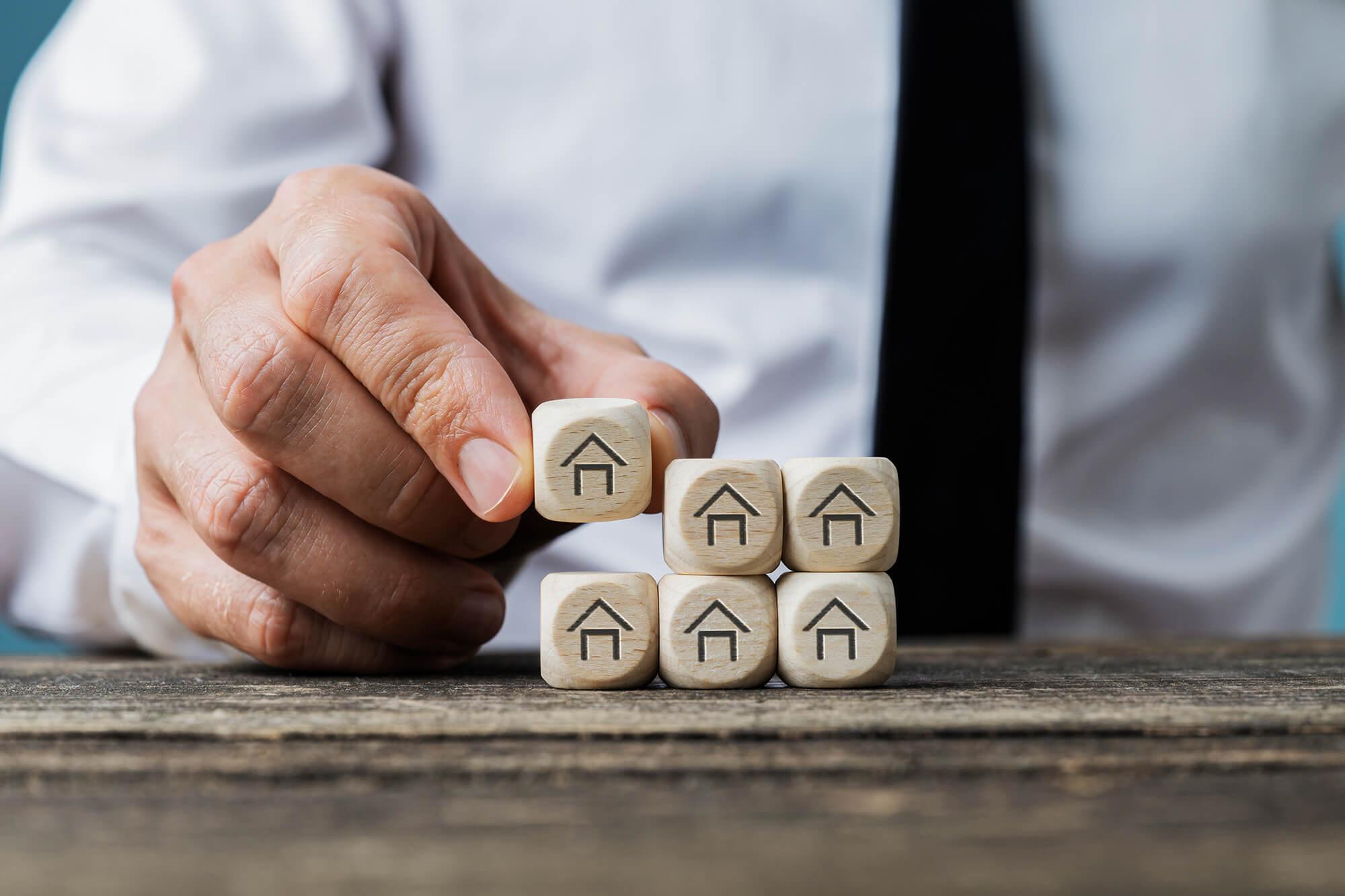 Eine Hand stapelt Würfel mit einem Haussymbol darauf