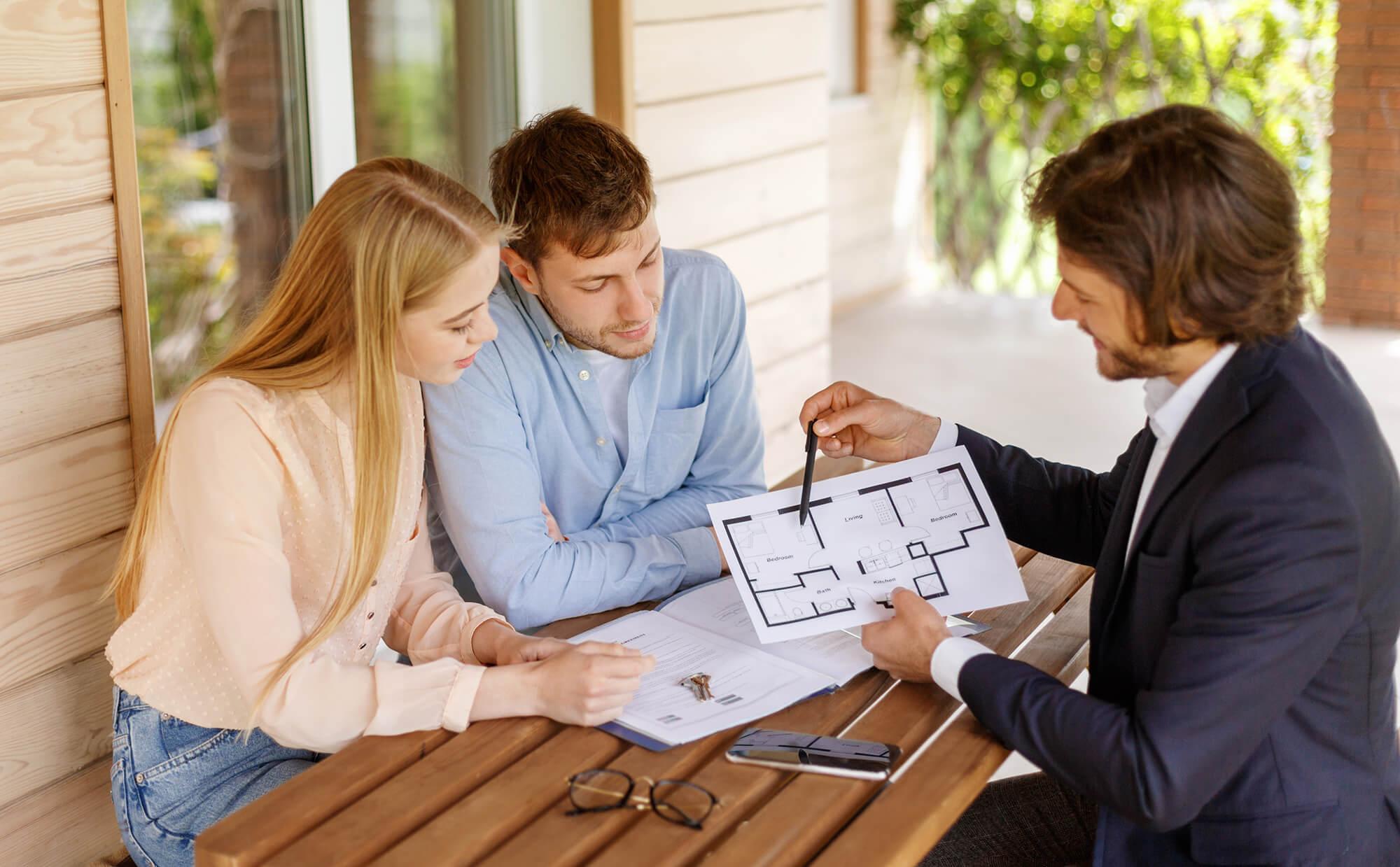 Immobilienmakler zeigt einem Ehepaar einen Grundriss