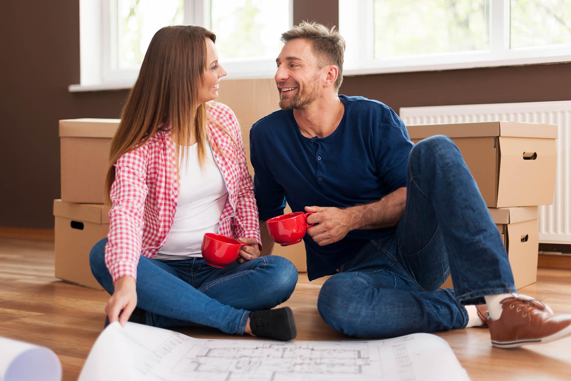 Glückliches Paar sitzt entspannt auf dem Holzboden. Hinter ihnen sind Umzugskartons zu sehen