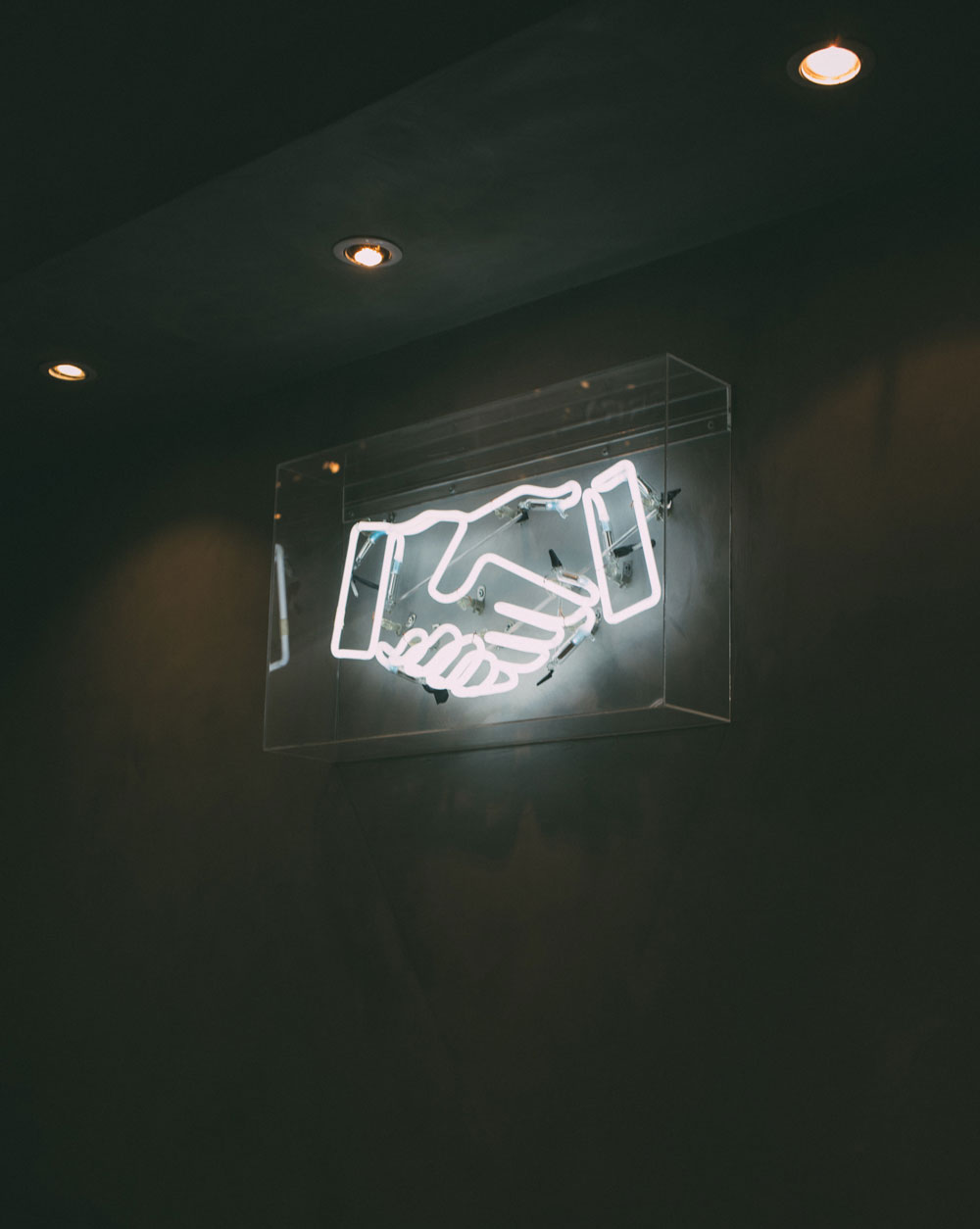 Neon sign of two hands shaking.