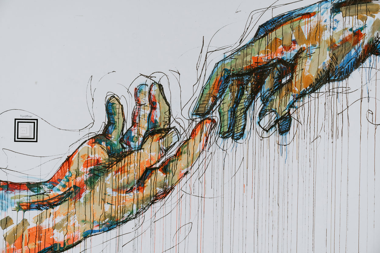 Colourful painting of two hands reaching out to each other.