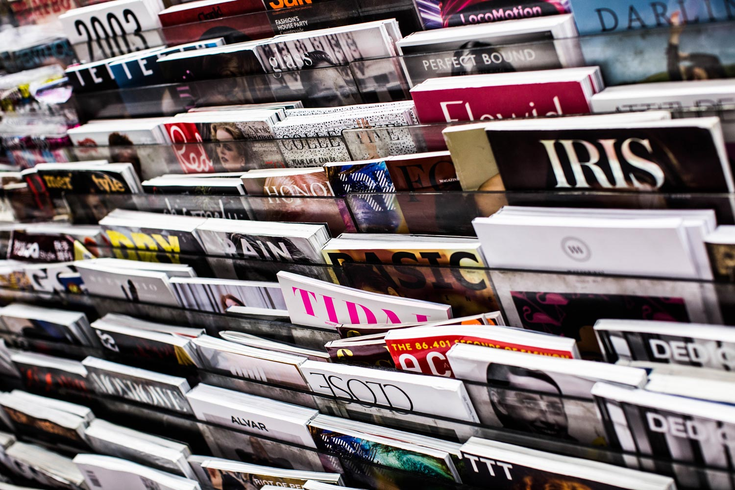 Closeup photo of a bunch of magazines on a rack.