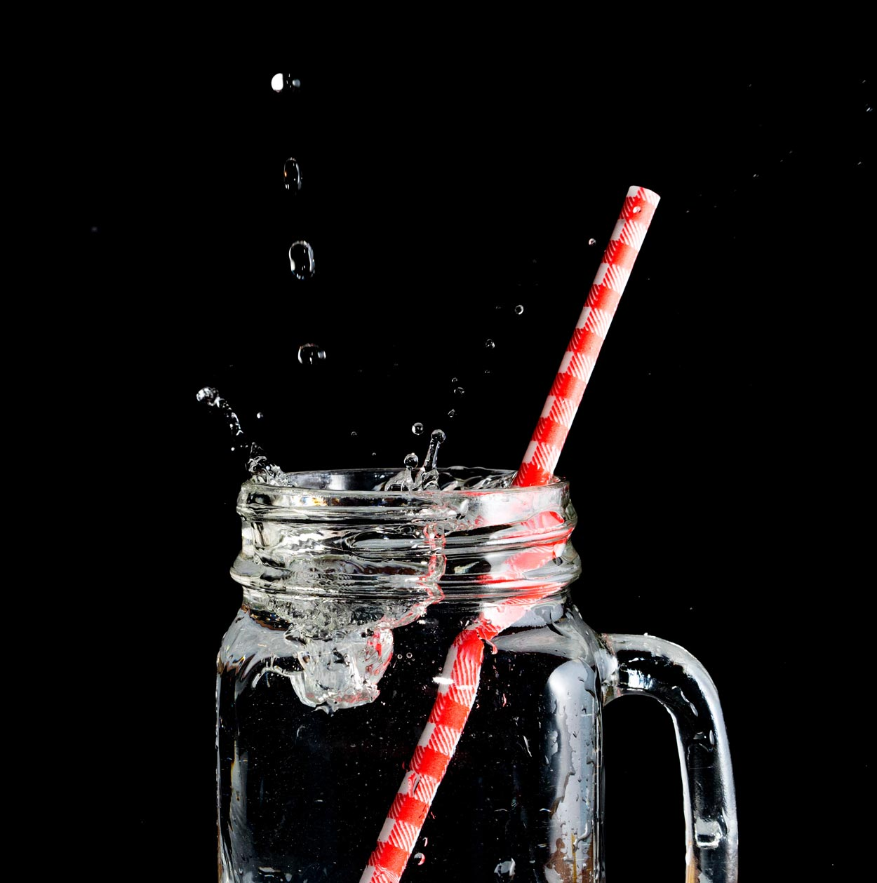 Photo of an ice cube being dropped into a mason jar full of water with a plastic straw.