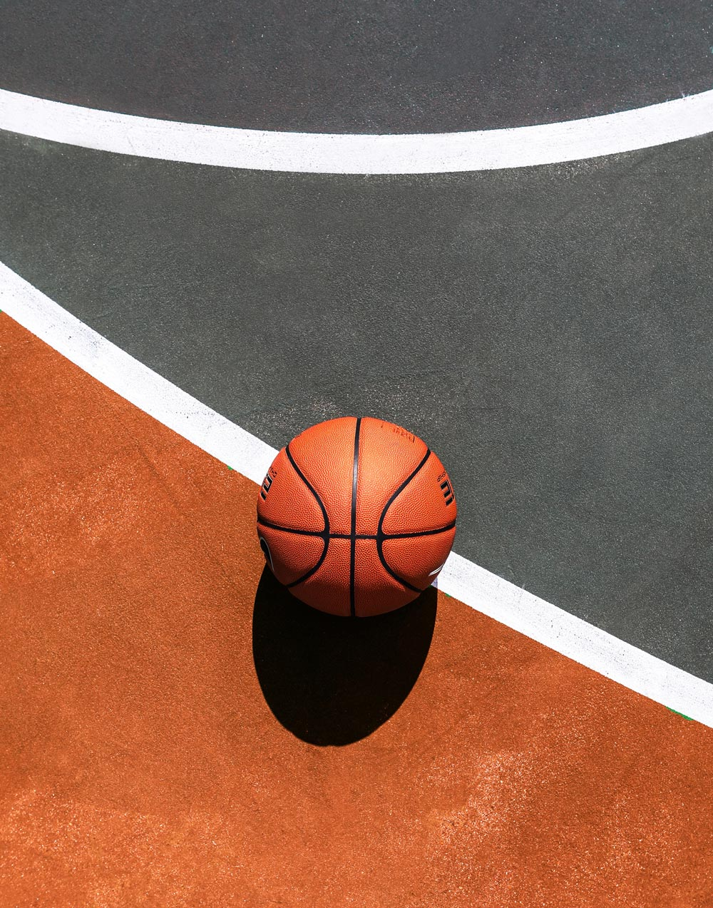 Topdown photo of a basketball on a sunny court.
