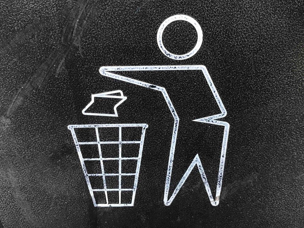Illustration of a man throwing garbage into a receptacle.
