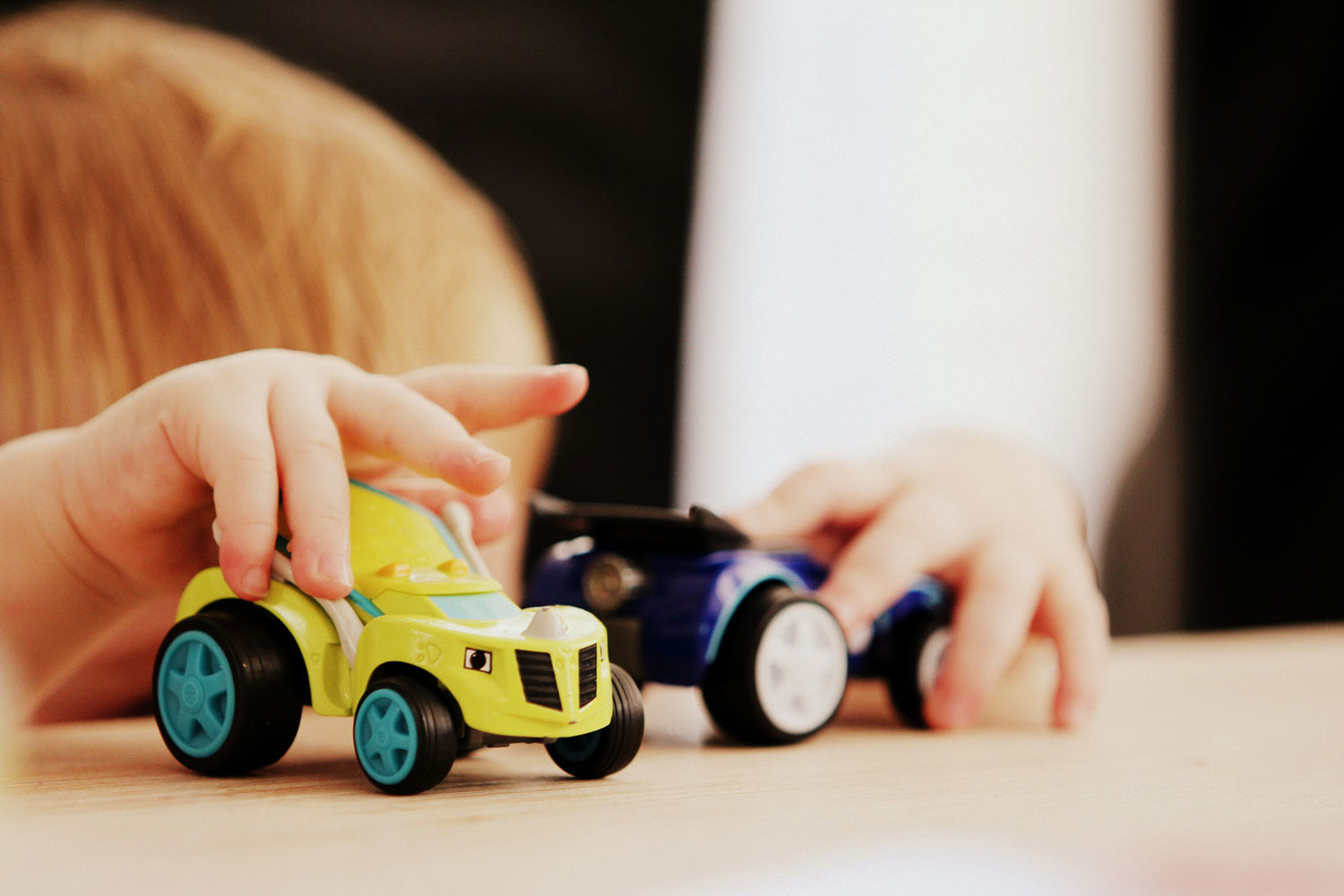 Closeup of a child's hands playing with some toy cars.