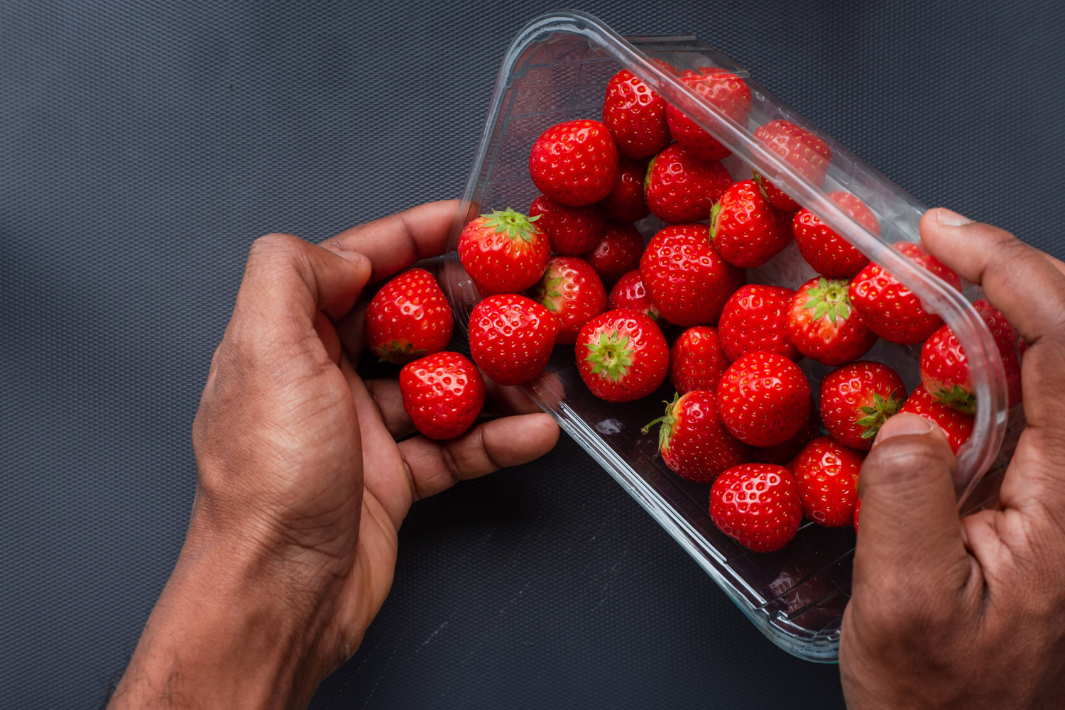 Photo of a person pouring strawberries from the plastic container into their hand.