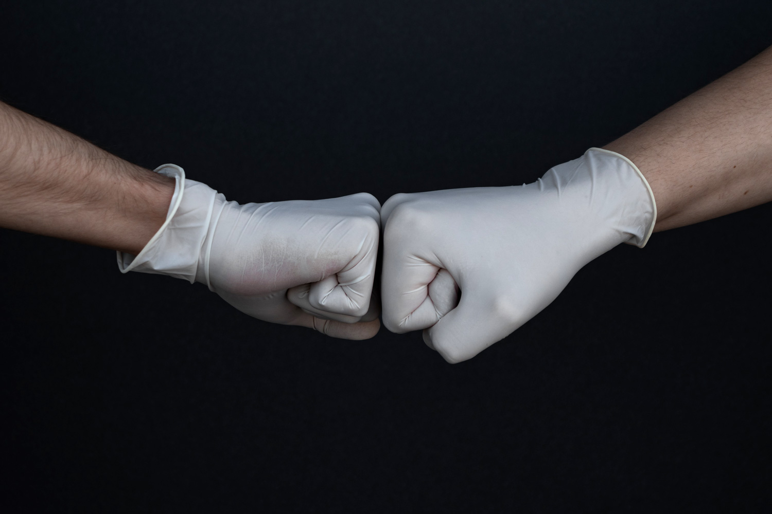 Photo of two gloved hands in fists touching each other.