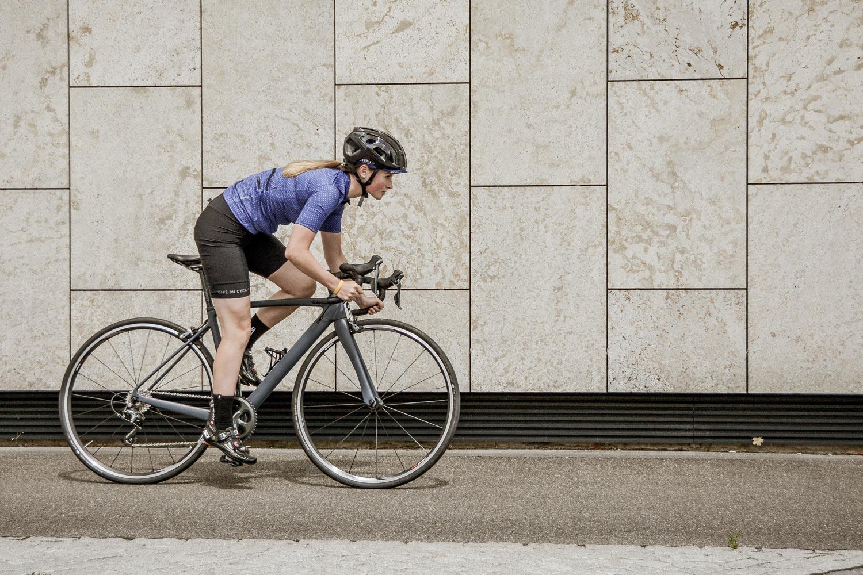 Photo of a cyclist biking on a sidewalk.