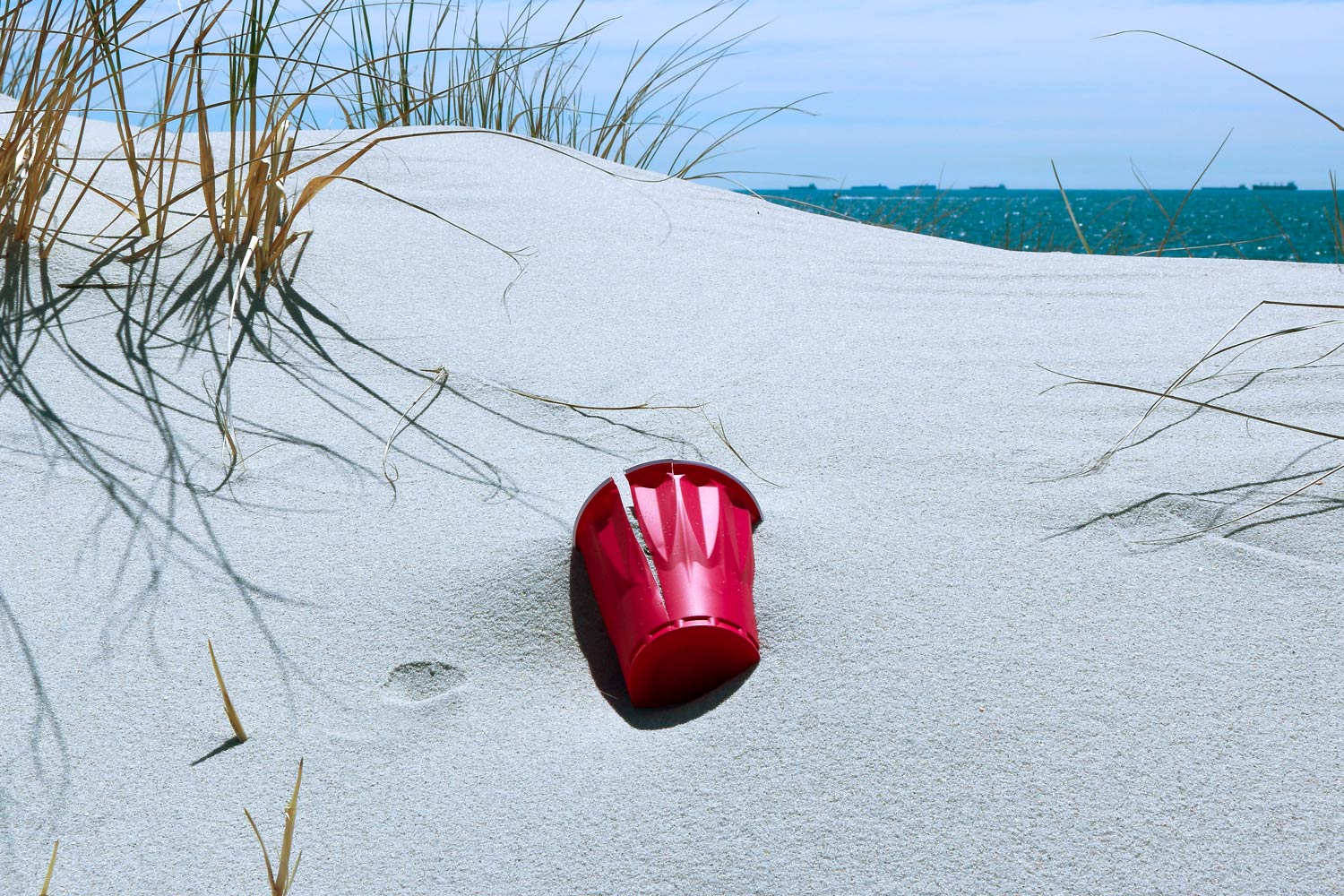 Photo of an old red plastic Solo cup on the beach.