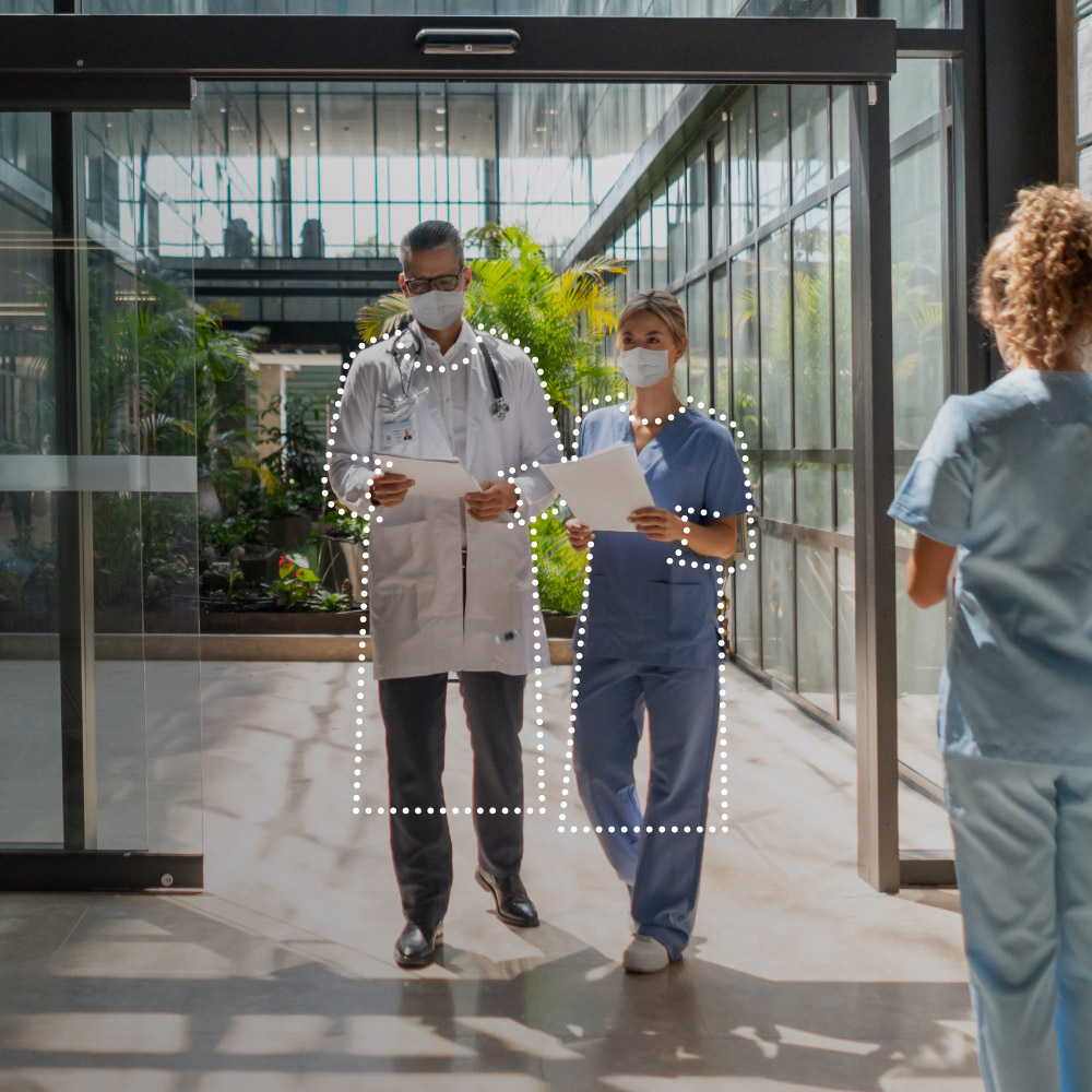 Photo of a doctor walking through a hallway with a dot-style illustration of a plastic protective garment overtop.