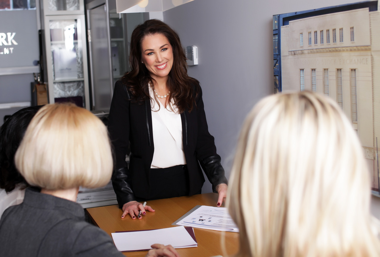 Photo of Karen Kelly meeting with a group of clients in an office setting