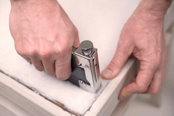 Hands stapling material to frame