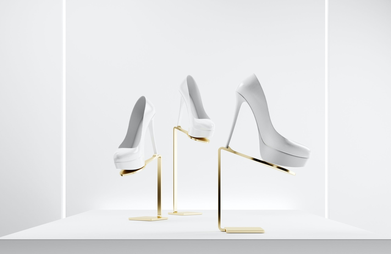 Three white shoes presented  on satin brass shoe displays by Ec Studio for visual merchandising