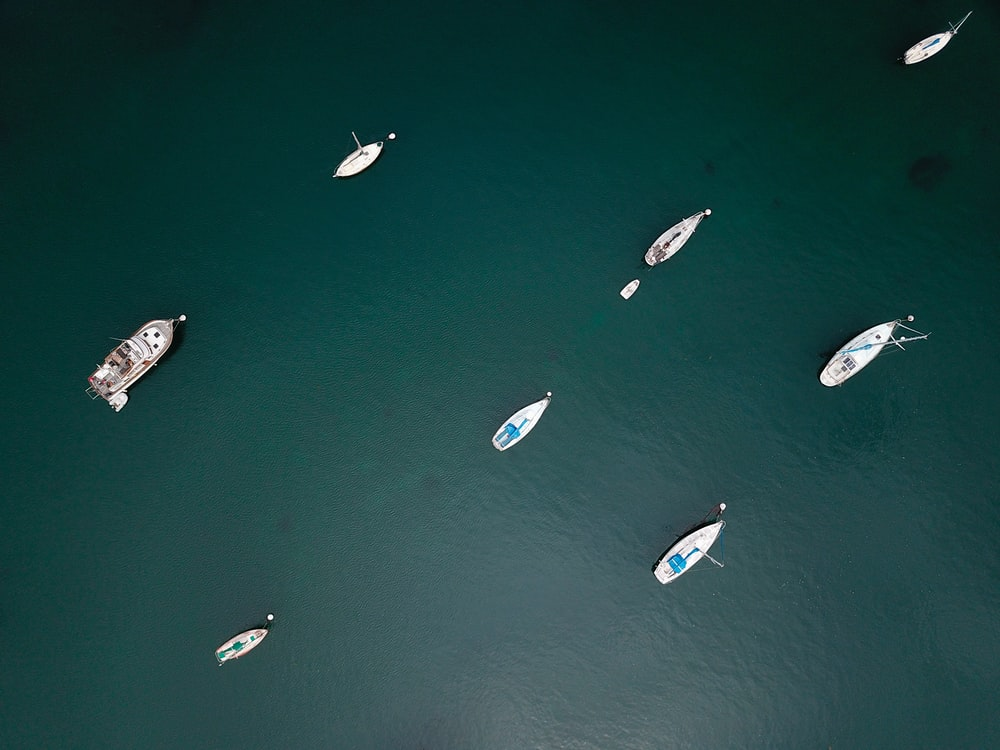 aerial photo of boats on calm body of water during daytime