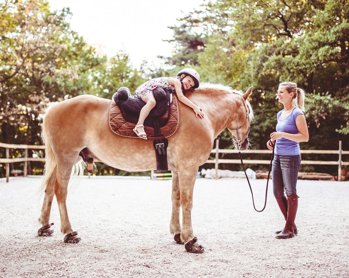 Girl hugging horse while instructor smiles