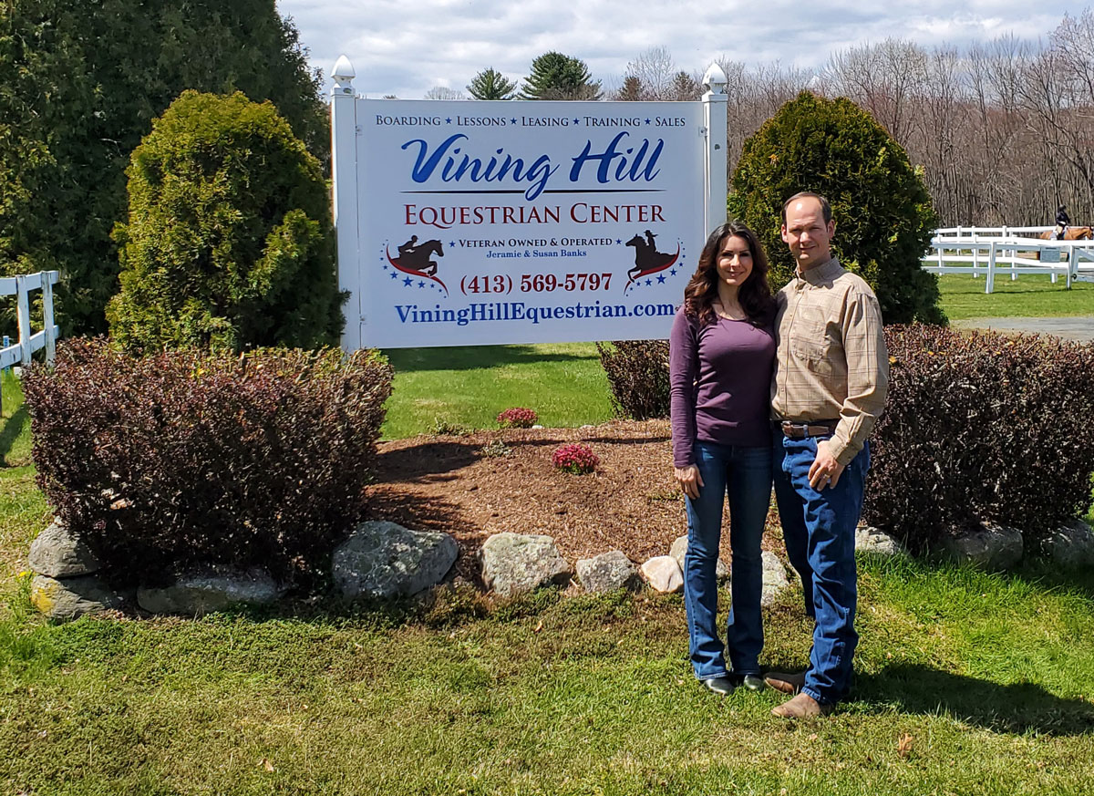 Jeramie and Susan Banks in front of their business sign