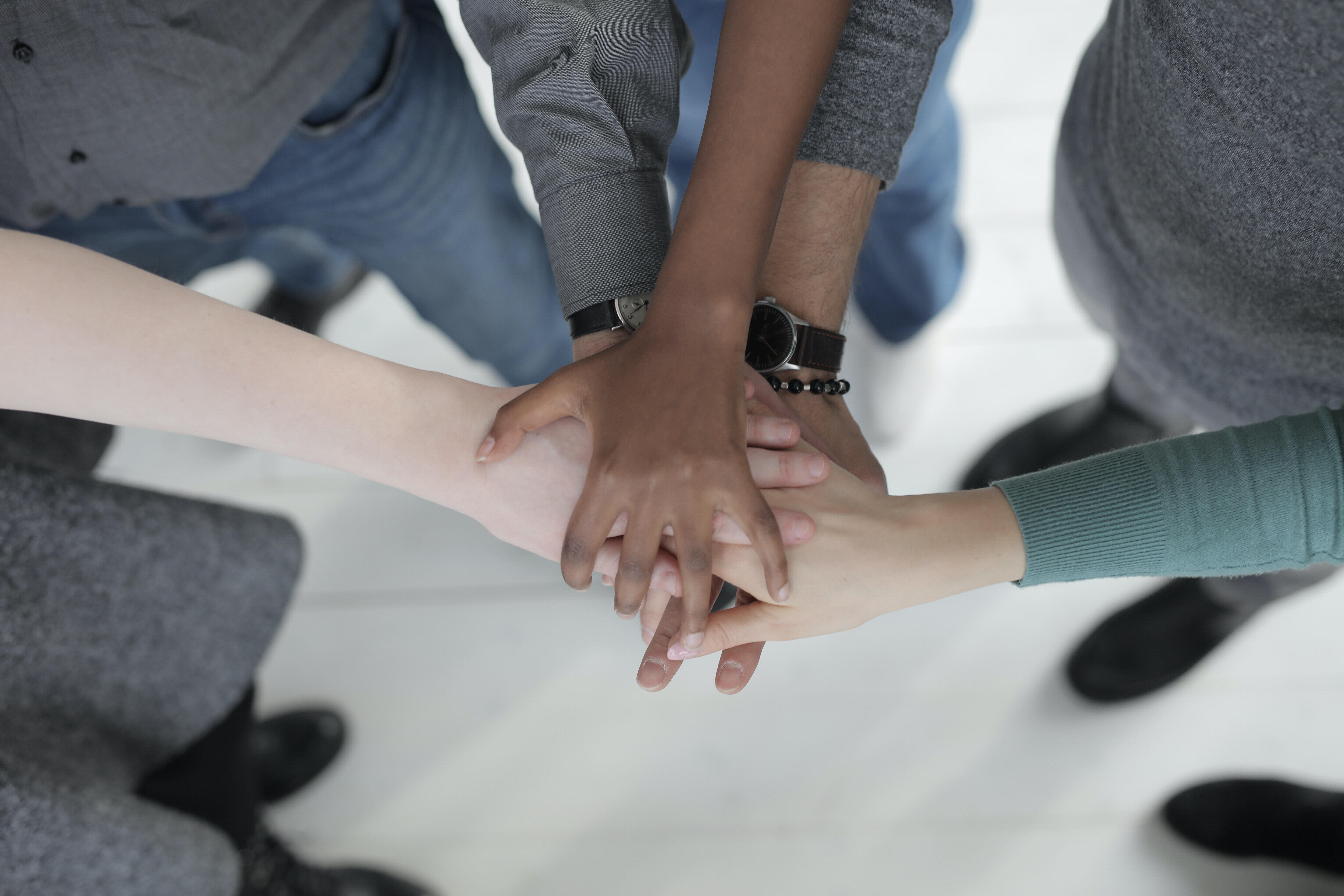 Multiethnic group shakes hands