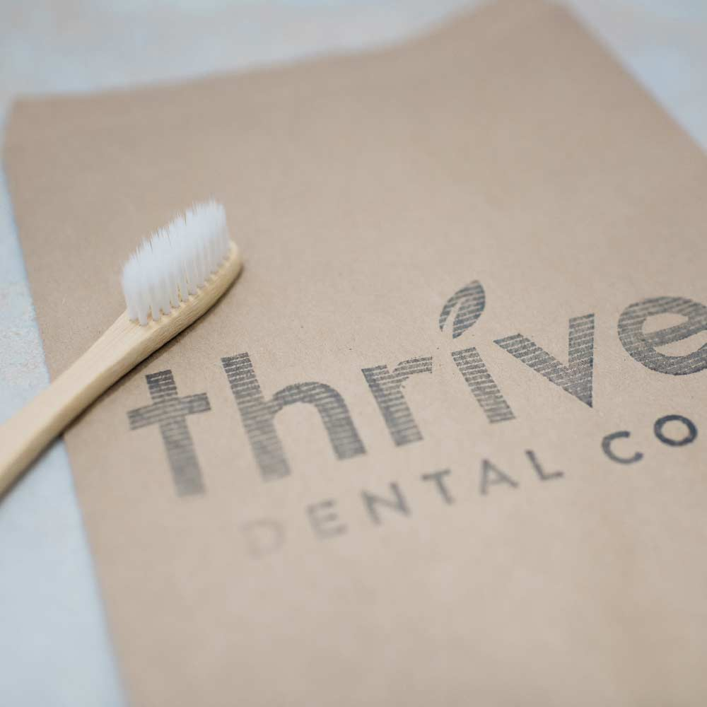 Photo of a Thrive Dental Co. notebook with a bamboo toothbrush sitting on top
