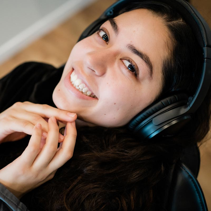 Photo of a smiling patient wearing headphones